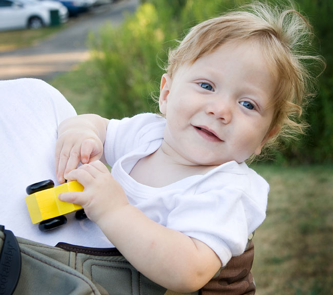 photo of a baby with a wooden car, riding in a sling