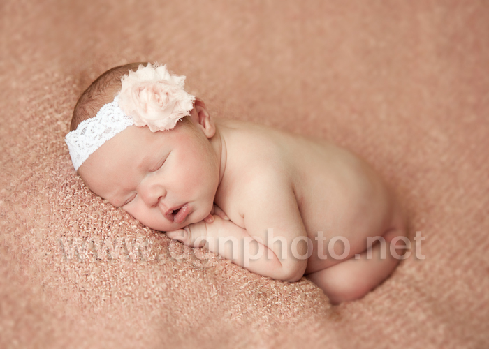 newborn baby girl sleeping wearing a headband