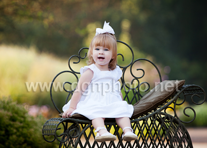 Miss D at the park in her little white dress and bow (the green bench was brought from the photographer's studio)